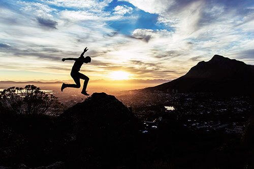 Silhouette of a person leaping through the air during sunset.