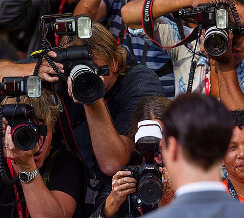 Photographers taking pictures of a man at a podium.