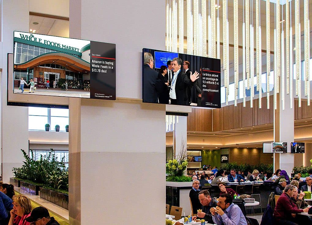 Neo Traffic screens displaying The Canadian Press news on digital screens in a mall foodcourt