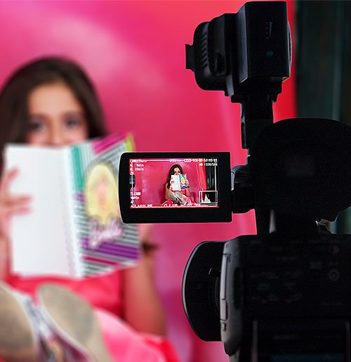 Woman holding a book in front of her face being recorded by a video camera.