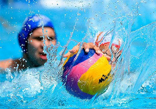 Two sport swimmers reaching for a ball in a pool.