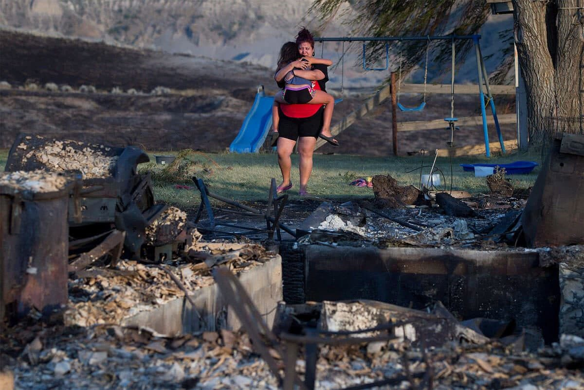 Kelsey Thorne holds her daughter Nevaeh Porter, 8, as they both cry while viewing the remains of their home where they lived with her parents that was destroyed by wildfire on the Ashcroft First Nation, near Ashcroft, B.C., late Sunday July 9, 2017