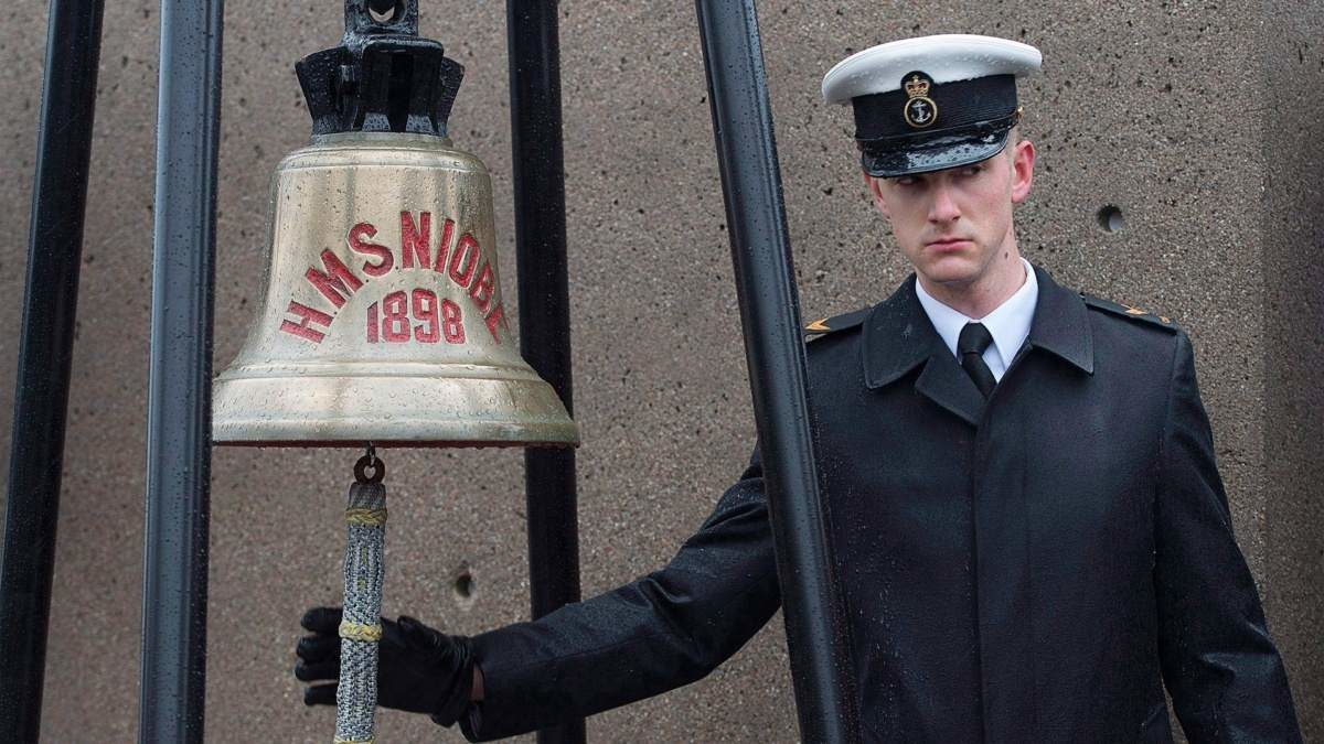 a sailor rings a bell on the anniversary of the Halifax Explosion
