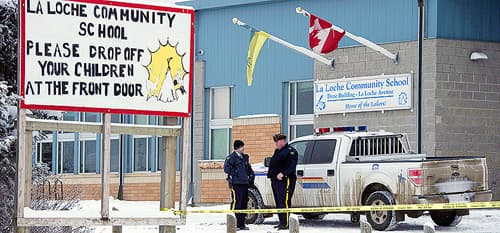 Two police officers stand out front of La Loche Community School