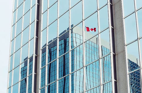 A Canadian Flag reflected in the modern glass of a business tower