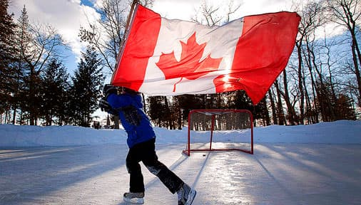 A boy skating on a frozen pond with a Canadian flag tied to a hockey stick