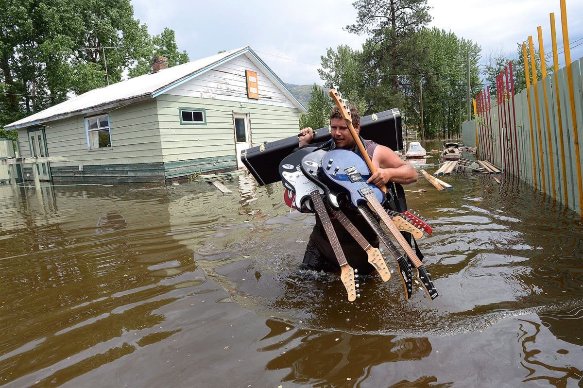 Lars Androsoff carries his friend's guitars as he walks through the floodwaters in Grand Forks, B.C.