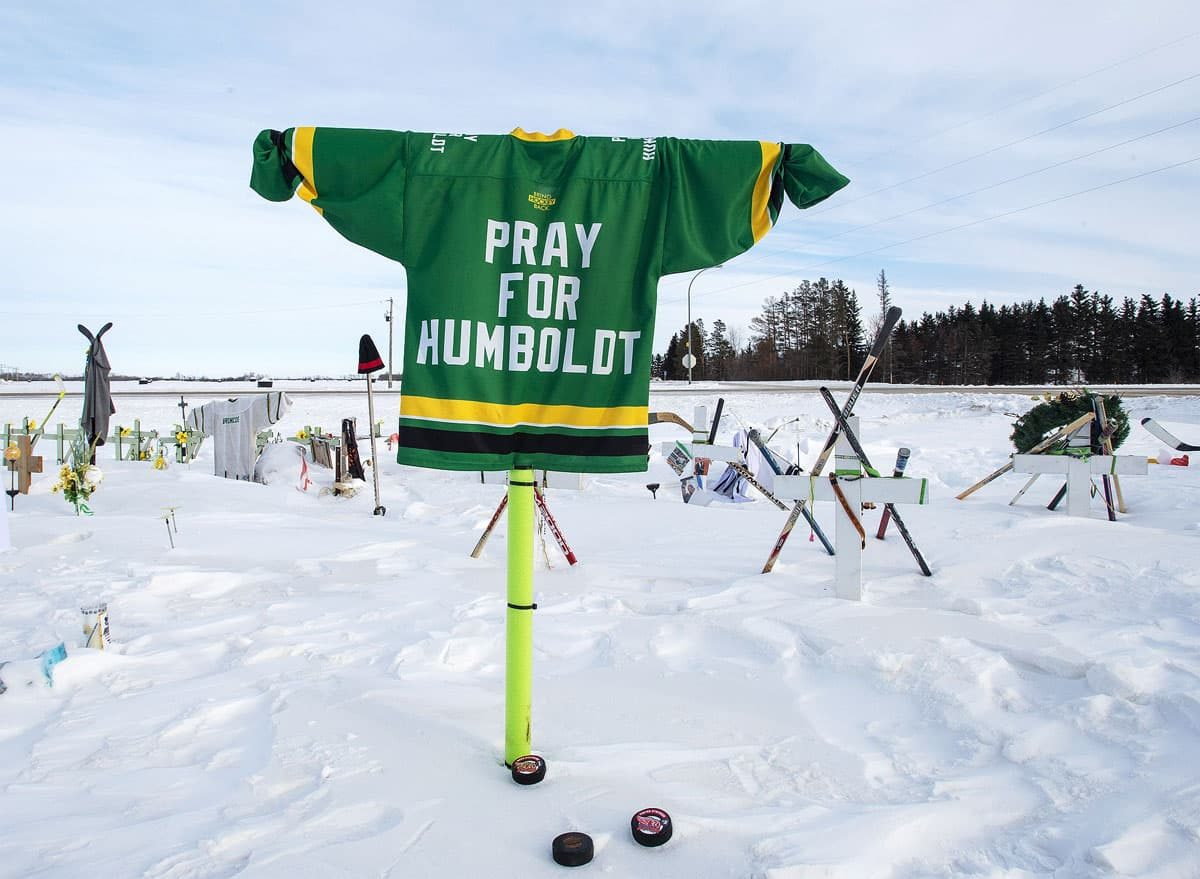 """A hockey jersey reading """"Pray for Humboldt"""" raised above the winter landscape near the sight of the crash."""