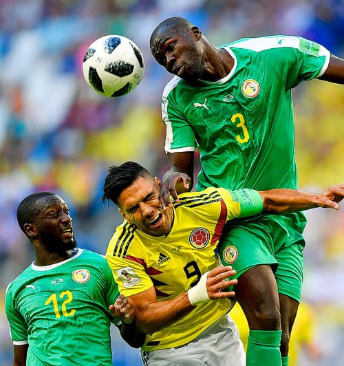 Colombia's Radamel Falcao, center, jumps for the ball with Senegal's Kalidou Koulibaly, right, and Senegal's Youssouf Sabaly, left, during the group H match between Senegal and Colombia