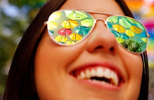 Umbrellas reflected in a gleeful woman's sunglasses