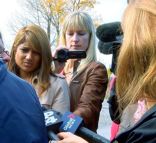 The Canadian Press reporter Allison Jones filing an interview outside with other reporters