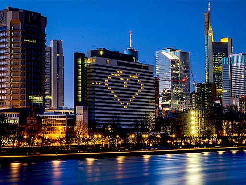 FOR HOLD ———File - In this Sunday, March 22, 2020 file photo, a hotel has switched on the lights in some rooms to form a heart near the buildings of the banking district in Frankfurt, Germany, as the German government announced new public restrictions to help avoid the spread of Coronavirus. For some people the COVID-19 coronavirus causes mild or moderate symptoms, but for some it can cause severe illness including pneumonia. Germany has hit another grim milestone in the coronavirus pandemic ticking above 1 million confirmed coronavirus cases. The Robert Koch Institute, the country's disease control center, said that Germany's 16 states reported 22,806 new cases overnight Friday, Nov. 27, 2020, for a total since the start of the outbreak of 1,006,394. (AP Photo/Michael Probst, file)