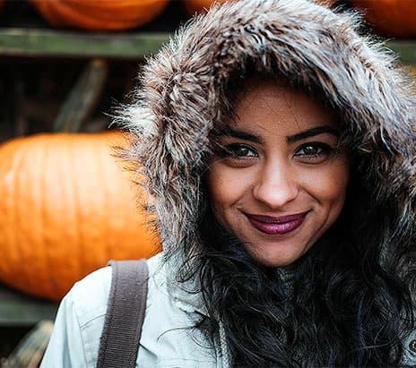woman smiling by pumpkin