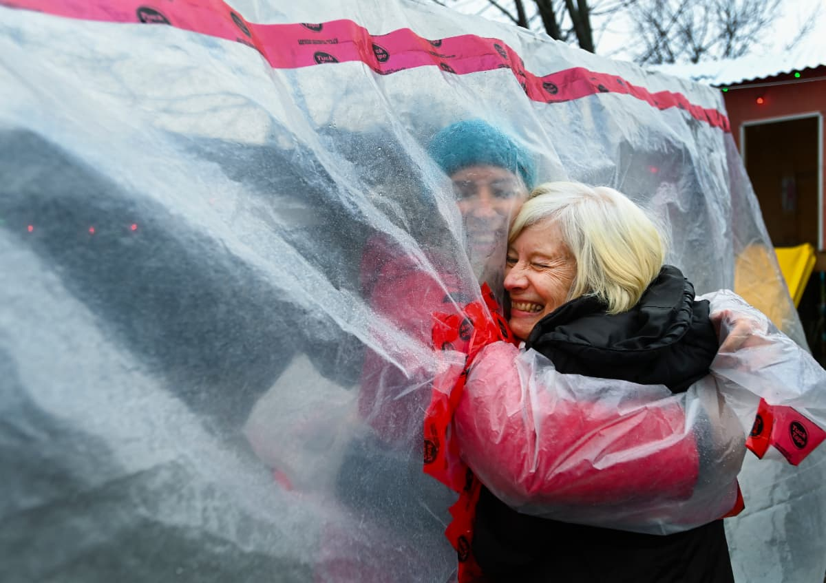 """a woman hugging her mother through a plastic """"hug glove"""" the woman created so the family could embrace despite COVID-19 restrictions"""