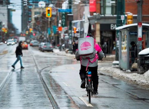 A foodora delivery driver navigates the streets of Toronto in winter