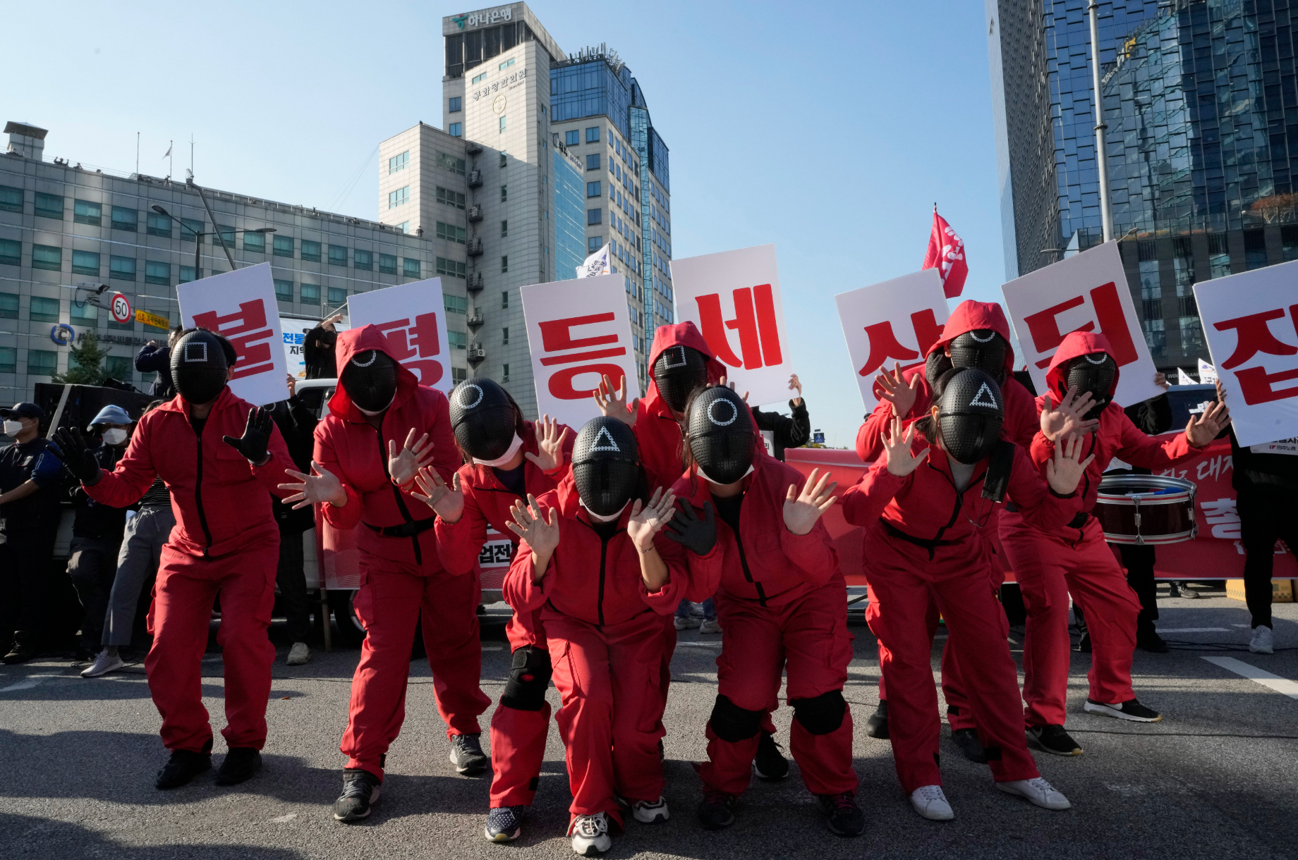 Protestors in South Korea dress as the guards from Squid Game