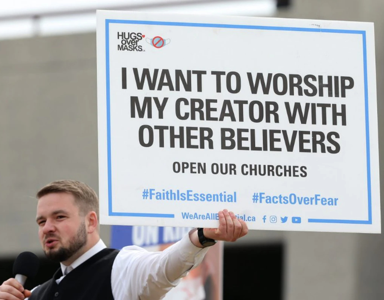 Tobias Tissen, minister at Church of God Restoration near Steinbach, holds a sign as he speaks during an anti-mask rally at The Forks in Winnipeg on Sun., April 25, 2021. KEVIN KING/Winnipeg Sun/Postmedia Network