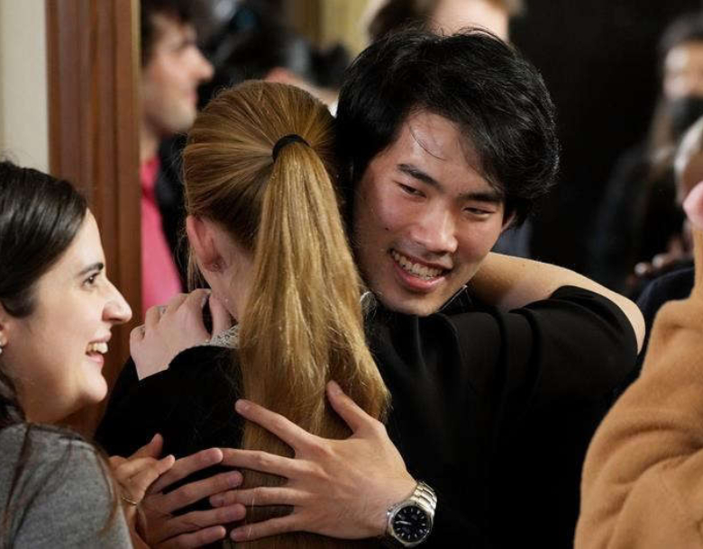Bruce Xiaoyu Liu is pictured hugging a friend with other friends surrounding him